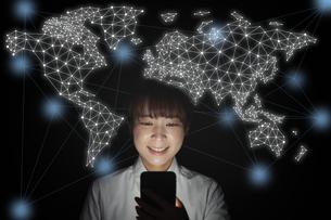 スマートフォンで世界と繋がる女性の写真素材 [FYI04109574]