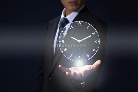 手から時計のホログラムを出すサラリーマンの写真素材 [FYI04109584]