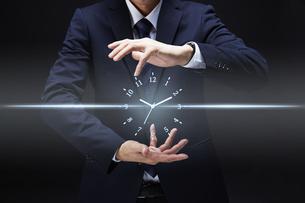 手から時計のホログラムを出すサラリーマンの写真素材 [FYI04109585]