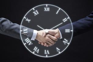 固い握手をするサラリーマンと時計のホログラムの写真素材 [FYI04109587]