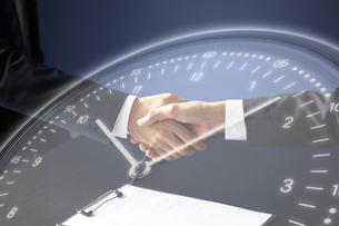 固い握手をするサラリーマンと時計のホログラムの写真素材 [FYI04109588]