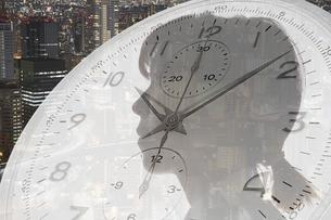 女性の横顔と時計と夜の街の写真素材 [FYI04109596]