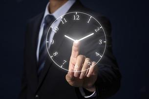 人差し指で時計に触れるサラリーマンの写真素材 [FYI04109597]