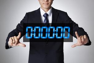 両手でデジタル時計のホログラムを囲むサラリーマンの写真素材 [FYI04109600]