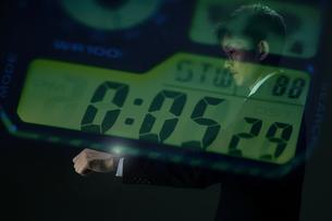 時間を確認する時計越しのサラリーマンの写真素材 [FYI04109602]