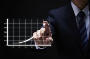 グラフのホログラムを指で操作するサラリーマンの写真素材 [FYI04109603]