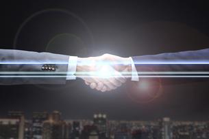 光を繋げる2人のサラリーマンの固い握手の写真素材 [FYI04109604]