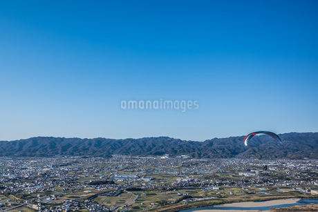 青空に向かって飛ぶパラグライダーの写真素材 [FYI04112398]