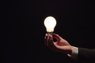 光る電球を持つサラリーマンの写真素材 [FYI04113139]