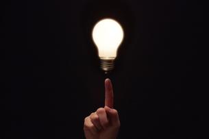 光る電球と指の写真素材 [FYI04113140]