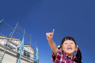 新築戸建て住宅をバックに元気に指差しをする幼い女の子。戸建て、新築、不動産、売買イメージの写真素材 [FYI04114517]