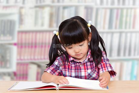 図書館で読書する幼い女の子。読書、勉強、興味、集中イメージの写真素材 [FYI04114518]