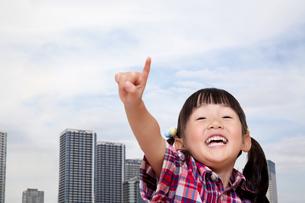 タワーマンション群をバックに元気に指差しをする幼い女の子。タワーマンション、不動産、売買イメージの写真素材 [FYI04114522]