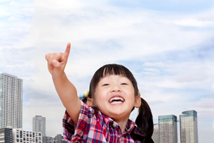 タワーマンション群をバックに元気に指差しをする幼い女の子。タワーマンション、不動産、売買イメージの写真素材 [FYI04114523]