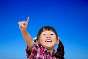 青空を背景に元気よく指差しをする幼い女の子。元気,前向き、快活イメージの写真素材 [FYI04114524]