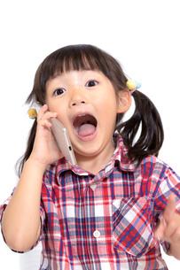 スマホを耳に当て驚き顔の幼い女の子。喜び、スマートフォン、驚きイメージの写真素材 [FYI04114530]