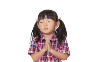 眼を閉じ祈る幼い少女。願い、祈願、祈りイメージの写真素材 [FYI04114534]