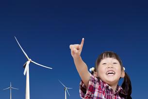 数機の風力発電機を前に笑顔で指差しをする幼い女の子。再生エネルギー、エコロジー、環境イメージの写真素材 [FYI04114545]