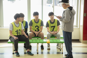 コーチを中心に作戦会議する若者たちの写真素材 [FYI04114726]