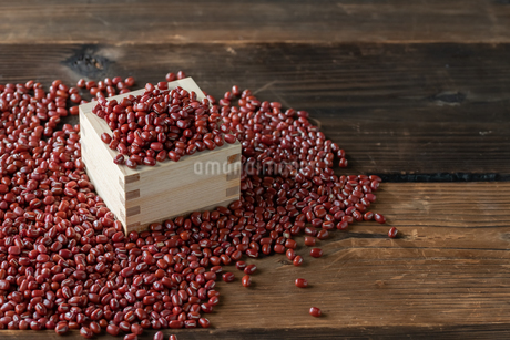 Red adzuki beans in square wooden measuring cup.の写真素材 [FYI04115088]