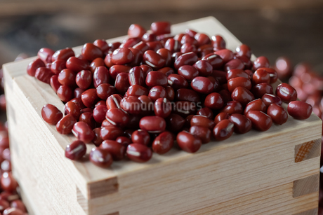 Red adzuki beans in square wooden measuring cup.の写真素材 [FYI04115089]