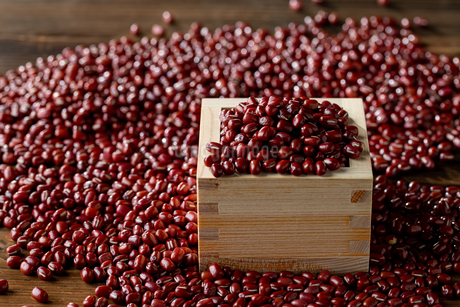 Red adzuki beans in square wooden measuring cup.の写真素材 [FYI04115390]