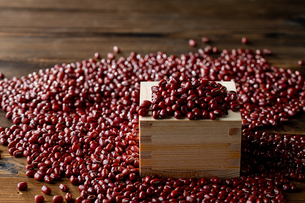 Red adzuki beans in square wooden measuring cup.の写真素材 [FYI04115391]