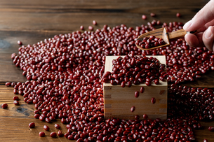 Red adzuki beans in square wooden measuring cup.の写真素材 [FYI04115393]