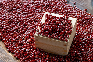 Red adzuki beans in square wooden measuring cup.の写真素材 [FYI04115396]