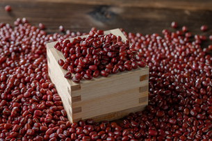Red adzuki beans in square wooden measuring cup.の写真素材 [FYI04115397]