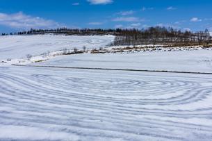 美瑛の丘の融雪作業の写真素材 [FYI04115745]