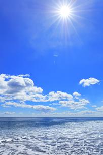 浜辺に寄せる波と空に太陽の写真素材 [FYI04115849]