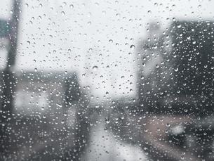 雨の日にビニール傘越しからみる町並み 雨粒の写真素材 [FYI04116042]