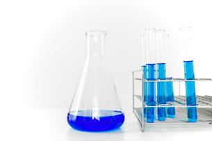 青い溶液の入った試験管とフラスコ。実験、開発、試験、検査イメージの写真素材 [FYI04116215]
