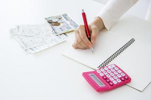 電卓、レシート、お金が置いてある家計イメージ。の写真素材 [FYI04116220]