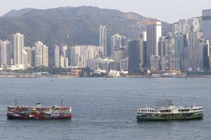 香港・ビクトリア湾を航行するスターフェリー。香港島と九龍半島の間で英国植民地時代から運行されている。左はビクトリア湾の観光船型のスターフェリーの写真素材 [FYI04116476]