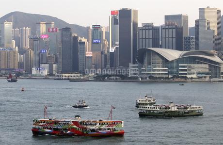 香港・ビクトリア湾を航行するスターフェリー。香港島と九龍半島の間で英国植民地時代から運行されている。左はビクトリア湾の観光船型のスターフェリーの写真素材 [FYI04116477]