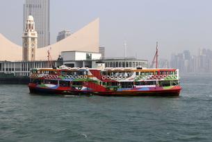 香港・ビクトリア湾を航行するスターフェリー。香港島と九龍半島の間で英国植民地時代から運行されている。これは観光船仕様にペイントされたスターフェリー。後方は英国植民地時代の九龍駅の時計台の写真素材 [FYI04117442]
