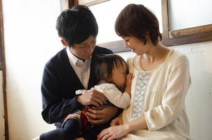 眠そうにしている子供と両親の写真素材 [FYI04117519]