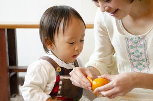 みかんを剥いている親子の写真素材 [FYI04117520]