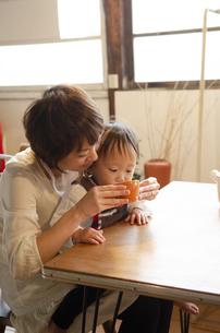テーブルでお茶を飲んでいる親子の写真素材 [FYI04117549]