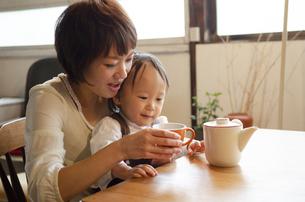 テーブルでお茶を飲んでいる親子の写真素材 [FYI04117551]