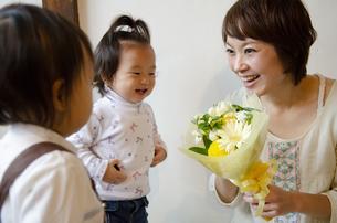 花束を持って笑っている母親と子供たちの写真素材 [FYI04117937]