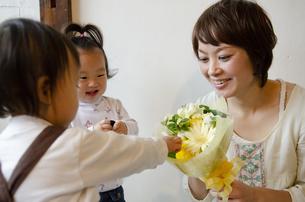 お花を持っている母親と子供たちの写真素材 [FYI04117938]