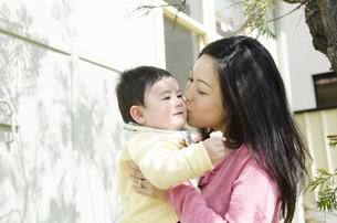 赤ちゃんの頬にキスをしている母親の写真素材 [FYI04117943]