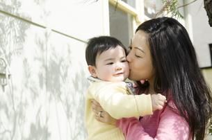 子供の頬にキスをしている母親の写真素材 [FYI04117945]