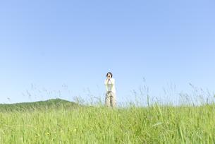 草原の中で声を出す女性の写真素材 [FYI04117973]