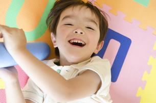 アルファベットマットの上で遊んでいる男の子の写真素材 [FYI04118021]