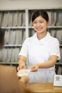 お薬手帳を渡す女性職員の写真素材 [FYI04118099]