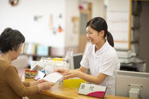 お薬手帳を渡す女性職員の写真素材 [FYI04118104]